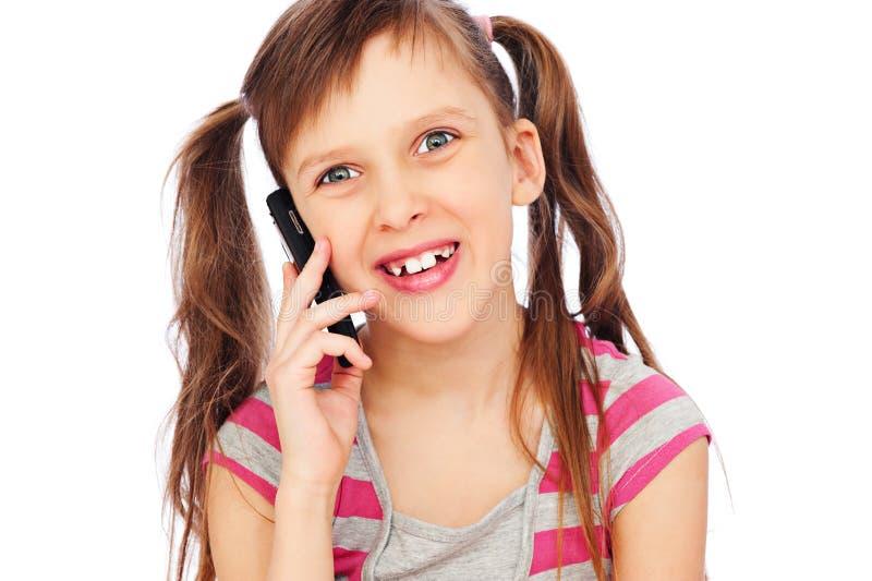 Lachendes kleines Mädchen mit Mobiltelefon stockfoto