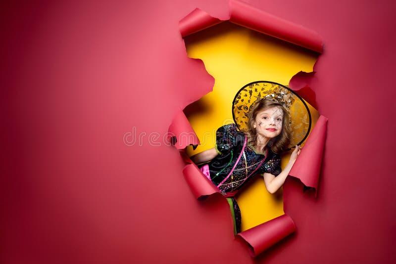 Lachendes lustiges Kindermädchen in einem Hexenkostüm in Halloween lizenzfreies stockfoto