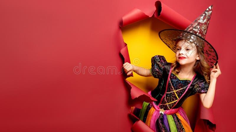 Lachendes lustiges Kindermädchen in einem Hexenkostüm in Halloween stockbilder
