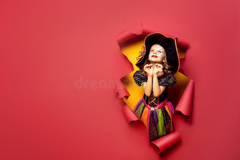 Lachendes lustiges Kindermädchen in einem Hexenkostüm in Halloween lizenzfreie stockfotos