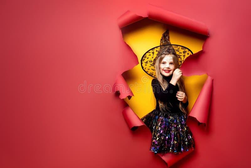 Lachendes lustiges Kindermädchen in einem Hexenkostüm in Halloween stockfotografie