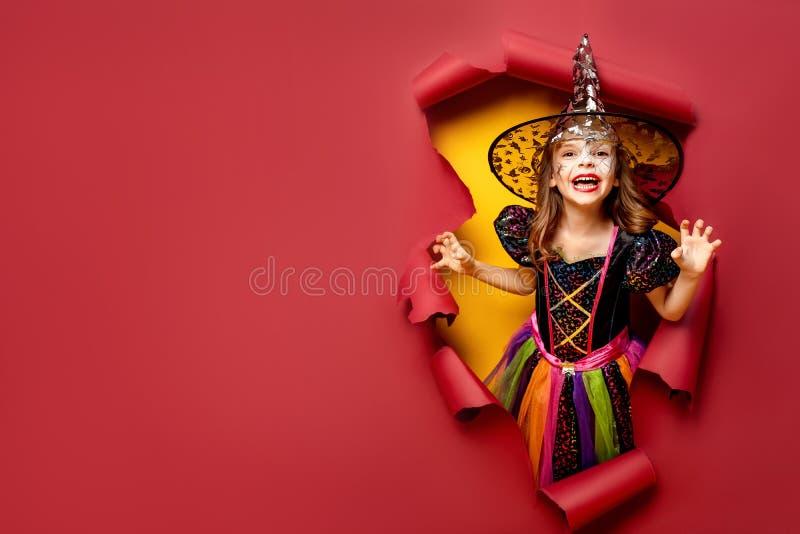 Lachendes lustiges Kindermädchen in einem Hexenkostüm in Halloween stockfotos