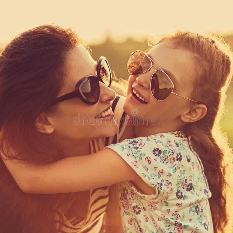 Lachendes Mädchen der glücklichen Mode Kinder, dasihre Mutter mit starker Liebe in der modischen Sonnenbrille lächelnd und auf Na stockfotos