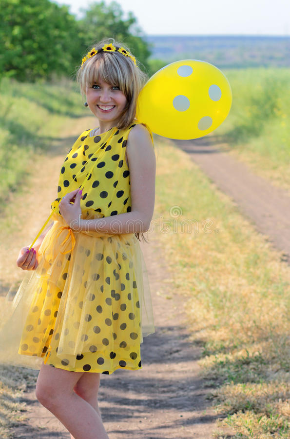 Lachendes Mädchen in einem gelben Kleid mit Tupfen mit dem Ball S lizenzfreies stockbild