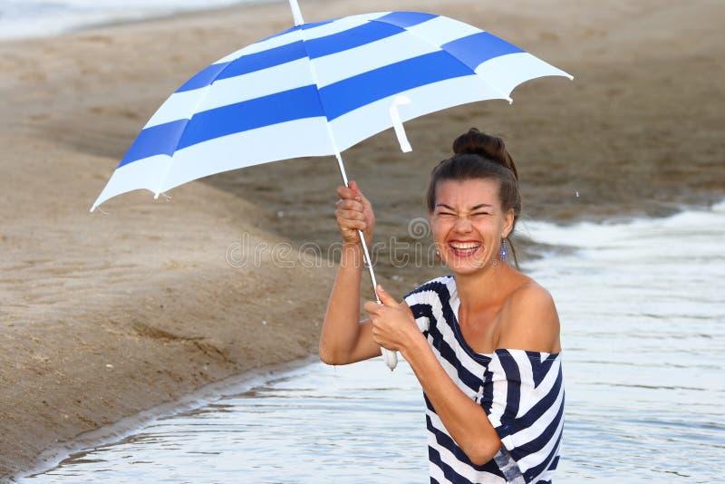 Lachendes Mädchen in einem gestreiften T-Shirt mit gestreiftem Regenschirm lizenzfreies stockfoto
