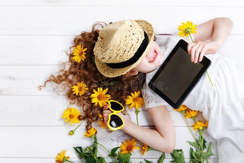 Lachendes Mädchen in einem Strohhut, der auf der Tablette in ihren Händen stillsteht stockbilder