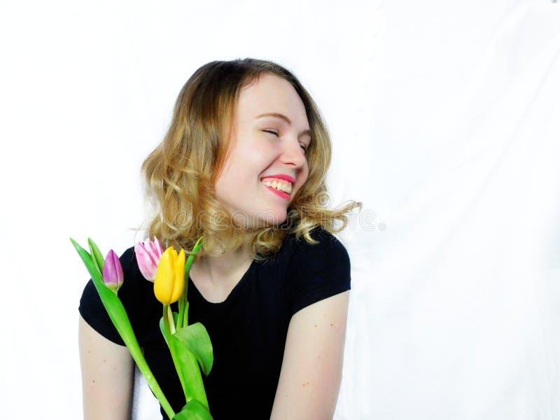 Lachendes Mädchen hält Blumenstrauß von Tulpen lizenzfreie stockbilder