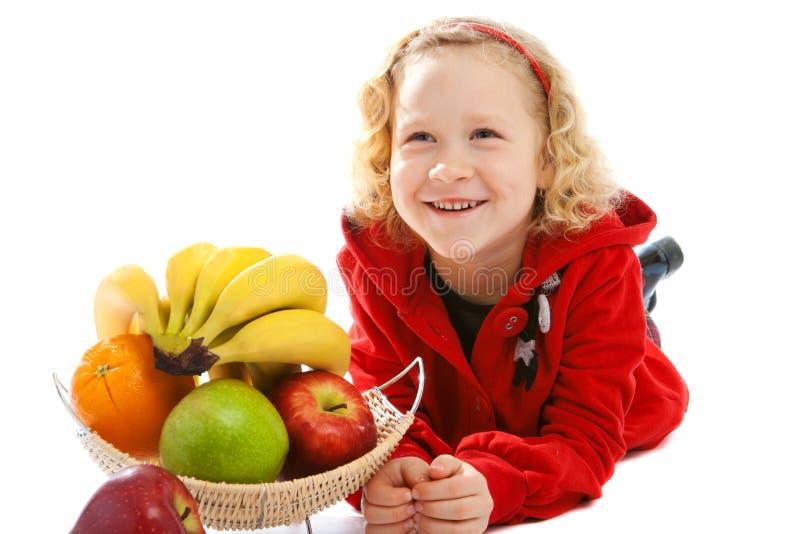 Lachendes Mädchen nahe Vase mit Frucht lizenzfreie stockfotografie