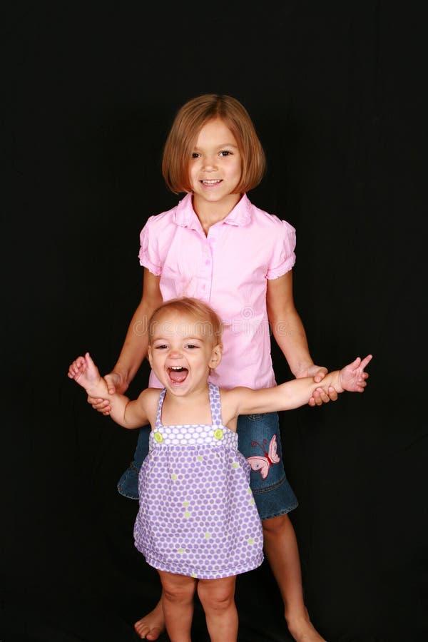 Lachendes Schätzchen und große Schwester lizenzfreie stockfotografie