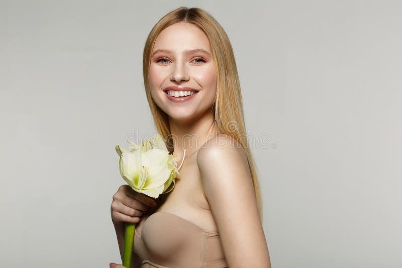 Lachendes schönes blondes Mädchen, das mit großer weißer Blume aufwirft stockbild