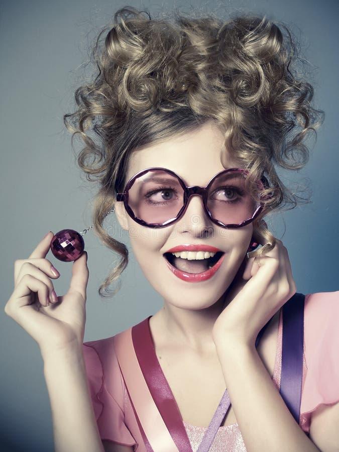Lachendes schönes Mädchen in den rosafarbenen Gläsern, Retro- stockfotografie