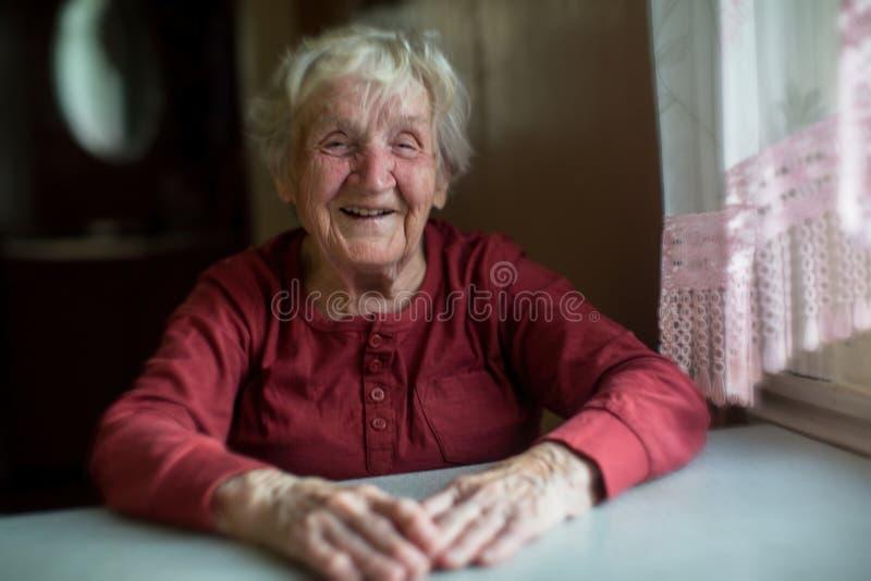 Lachendes Sitzen der älteren Frau am Tisch lizenzfreies stockbild