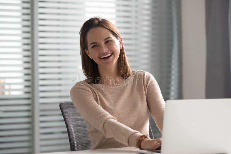 Lachendes Sitzen der glücklichen jungen Geschäftsfrau am Arbeitsschreibtisch mit Laptop lizenzfreies stockbild