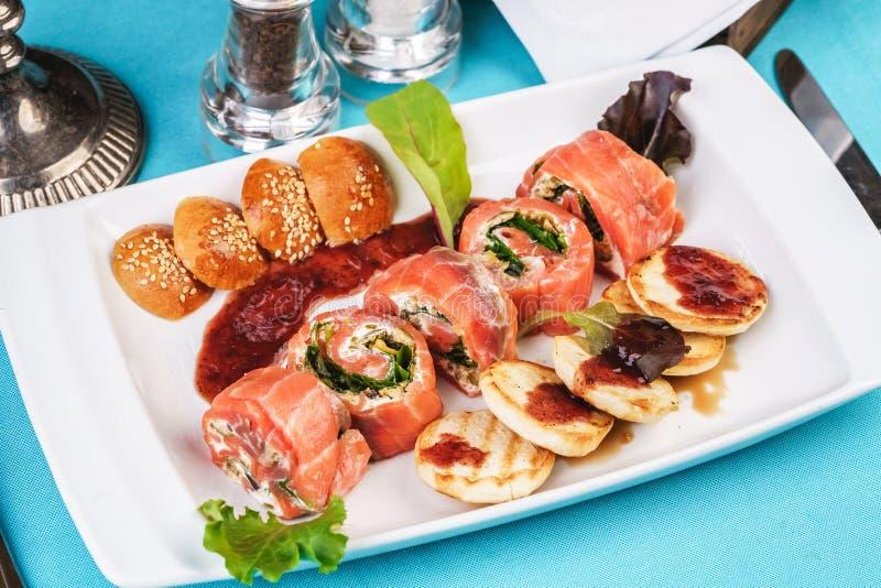 Lachs-Brötchen mit Käse und Grün in Chili-Sauce, serviert mit Pfannkuchen und Brötchen lizenzfreies stockfoto