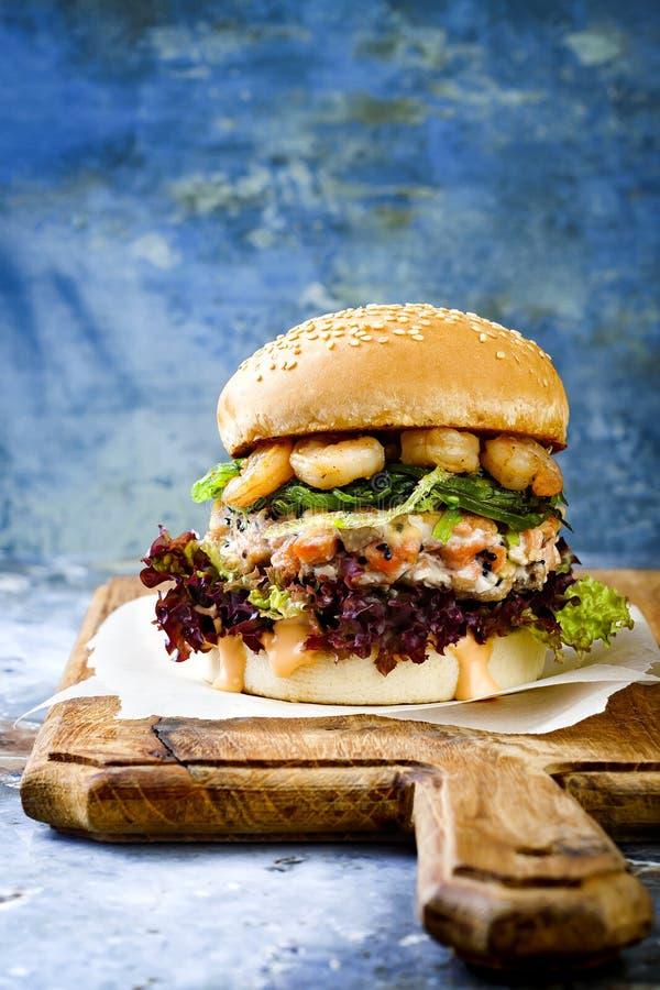 Lachsburger der asiatischen Art mit gegrillten Garnelen, Meerespflanze, Kopfsalat und würziger sriracha Mayo-Soße diente auf rust stockbilder