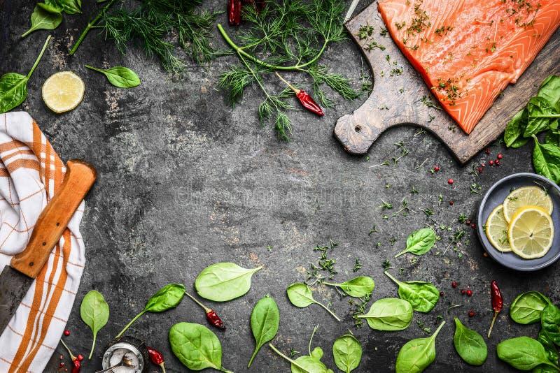 Lachsfischfilets auf Schneidebrett und frische Bestandteile für das Kochen auf rustikalem Hintergrund, Draufsicht lizenzfreie stockbilder