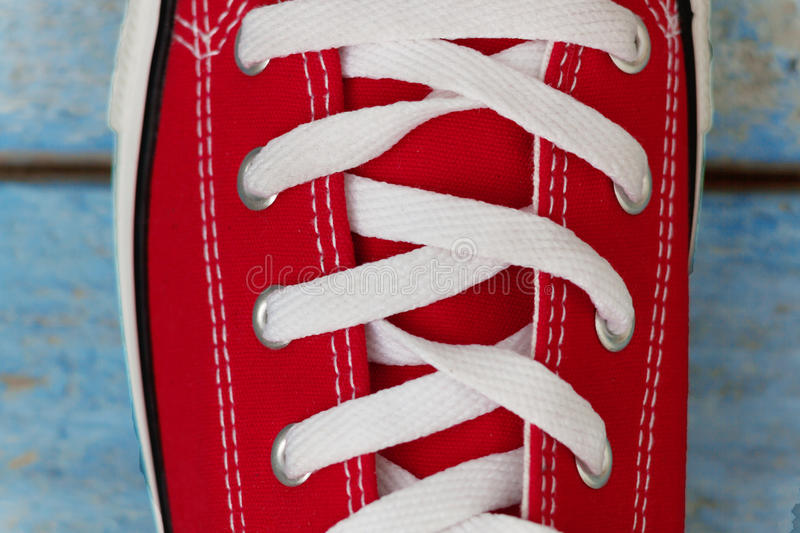 Lacing on a retro sneaker, close-up, on a blue wooden background stock image