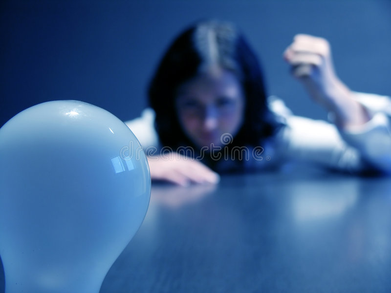 Lack of inspiration. Woman with a lack of inspiration. Focus on the bulb royalty free stock photography