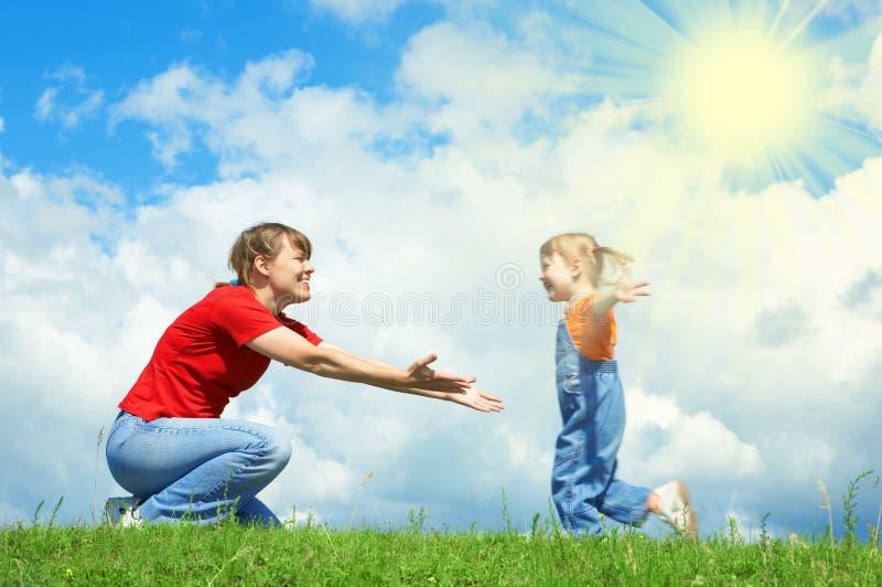 Lack-Läufer des kleinen Mädchens zur Mutterumarmung auf grünem Gras lizenzfreie stockbilder