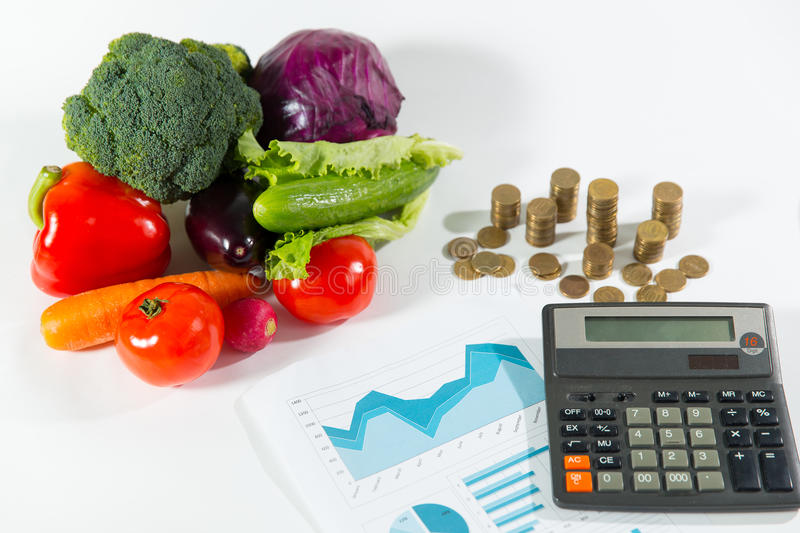 Lack of money on healthy food concept. Ripe vegetable composition against a stack of coins royalty free stock image