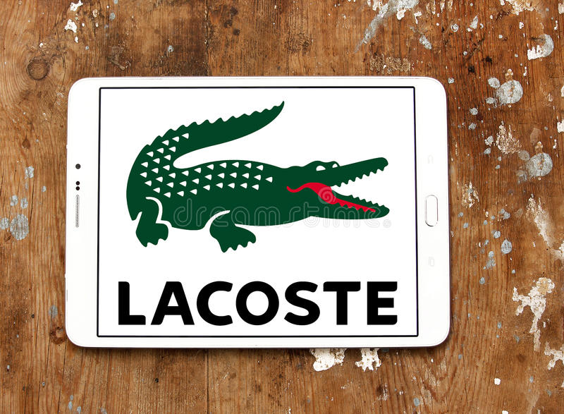 Lacoste logo. Logo of lacoste clothing company on samsung tablet on wooden background royalty free stock photos