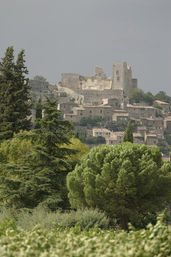 Lacoste village and castle in the Luberon, France. Lacoste in summer with full trees in bright sunshine. Lacoste is a commune in the Vaucluse department in the stock photos