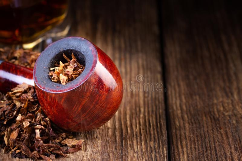 Lacquered smoking pipe and tobacco pile on vintage wooden table. royalty free stock photography