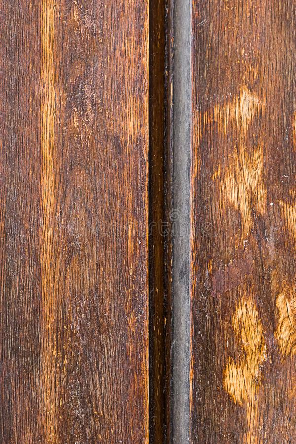 Lacquered vertical boards joint of two wooden brown panels frayed base monochrome substrate stock image