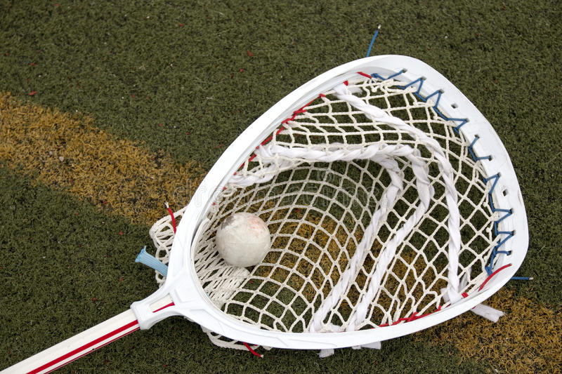Lacrosse goalie stick with ball in the net. A red and white lacrosse goalie stick on a green turf field with a ball in the net stock photography