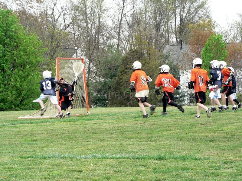 Lacrosse - little league game. A Little League game of Lacrosse being played. All identifying marks have been removed! Action blur is aplied to the shot stock photos