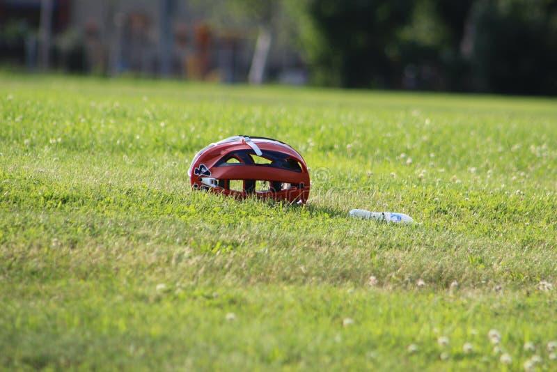 Lacrossehjälm på ett gräsfält, med vattenflaskan royaltyfria bilder