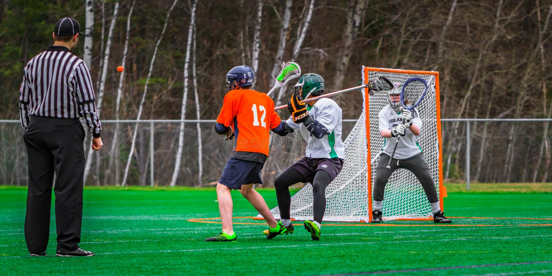 Lacrossesportspieler auf dem Gebiet stockfotos