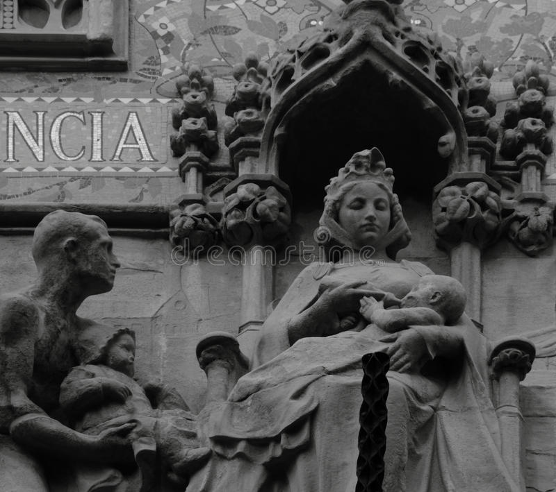 Lactation. Shot in black and white, detail on an sculpture representing a female figure placed on the facade of this historic building, set in Eixample royalty free stock image