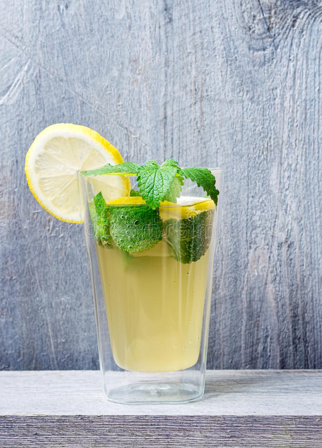 Lacto-fermented Soft Drink. Homemade lacto-fermented refreshing drink with lemon slices and sprigs of mint and lemon balm royalty free stock image