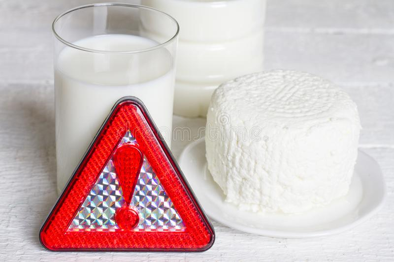 Lactose intolerance with milk dairy product and warning sign concept royalty free stock photography