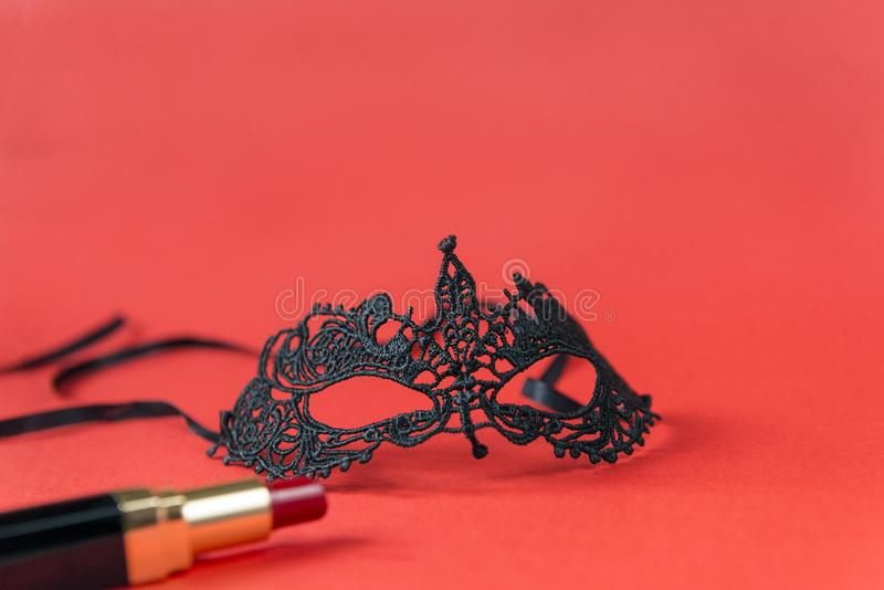 Lacy black mask, red lipstick with black case on red background. 1 Lacy black mask, red lipstick with black case on red background stock photo