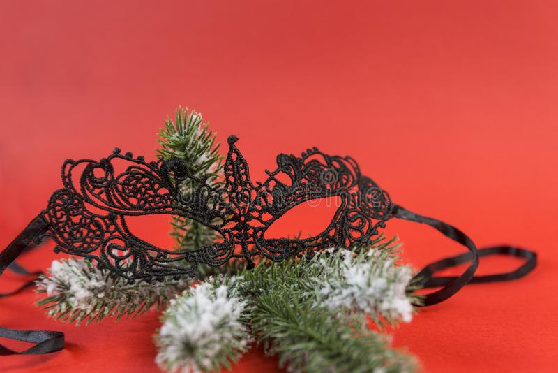 Lacy black mask on spruce branch on red background,. 1 Lacy black mask on a fir branch on a red background, Christmas decor royalty free stock photo