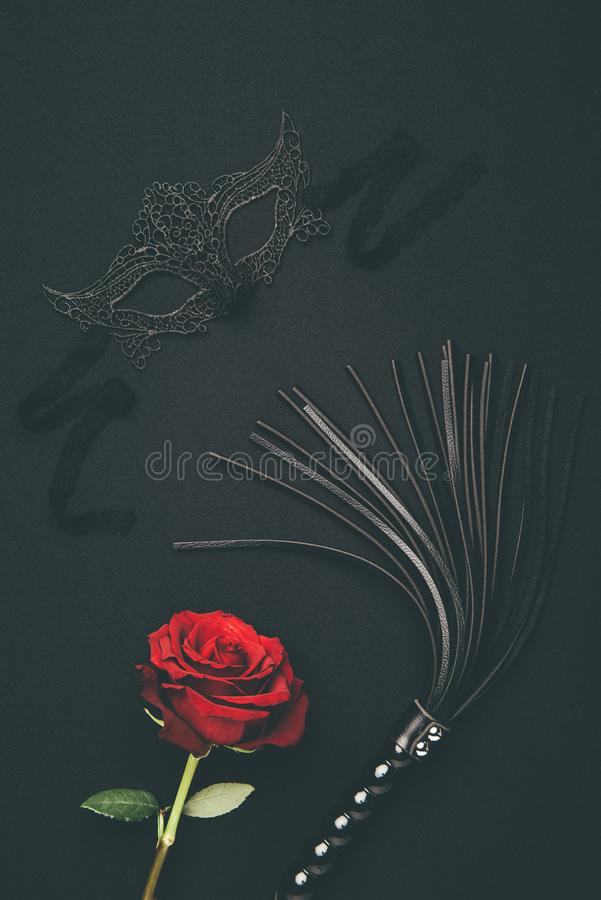 Lacy mask and black whip with rose flower stock photo