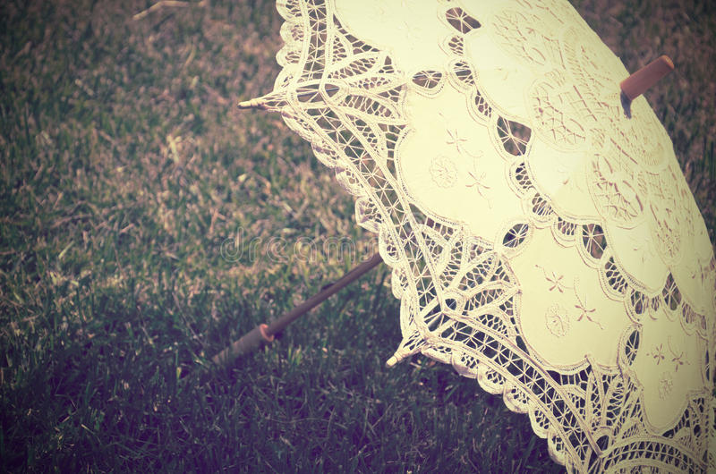 Lacy parasol on the grass close up. tinted vintage royalty free stock image