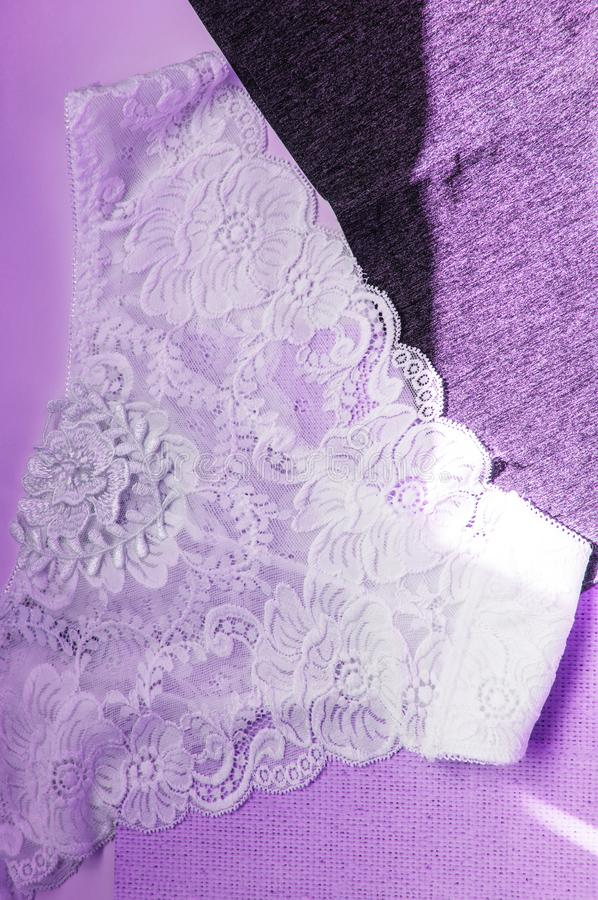 Lacy white sexy women`s panties on purple neon background. Vertical shot, top view, flat lay.  stock photos
