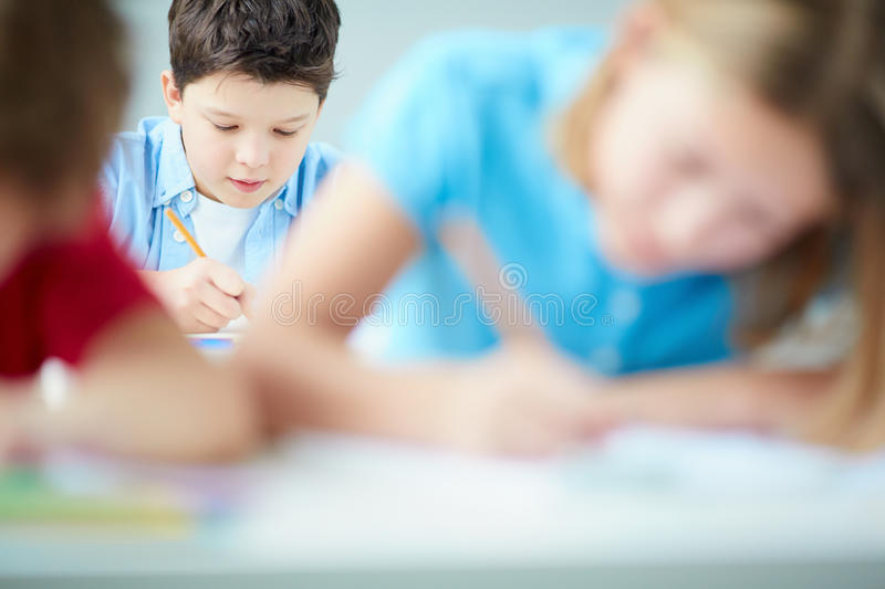 Lad drawing. Portrait of cute schoolboy drawing at lesson stock photos