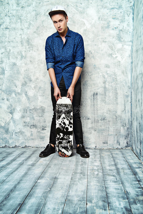 Lad with skateboard. Modern teen boy stands with his skateboard by a grunge wall royalty free stock image
