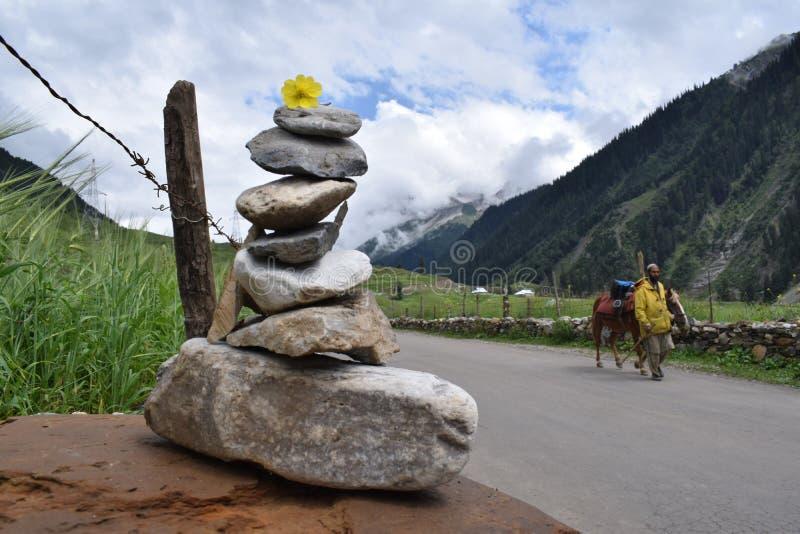 LADAKH, ДЖАММУ И КАШМИР, ИНДИЯ, июль 2018, местный пропуск человека каменной пирамидой сделанной со свободными камнями для удачи стоковая фотография rf