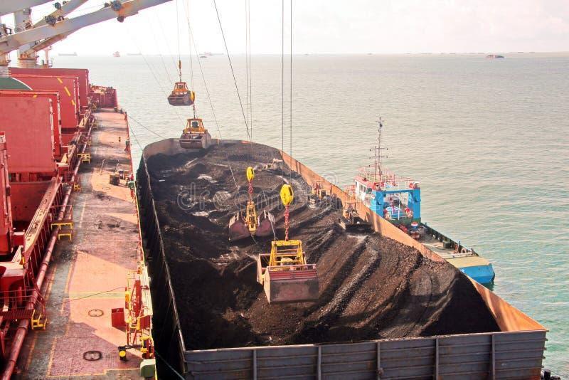 Ladda kol från lastpråm på en bärare som i stora partier använder skeppkranar och hastiga grepp på porten av Samarinda, Indonesie royaltyfri foto