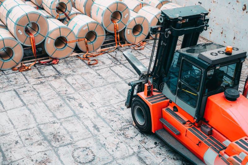 Ladda och lasta av process av stålspolar i lastport Bär den stål coilsRed lyftarmen arkivbilder
