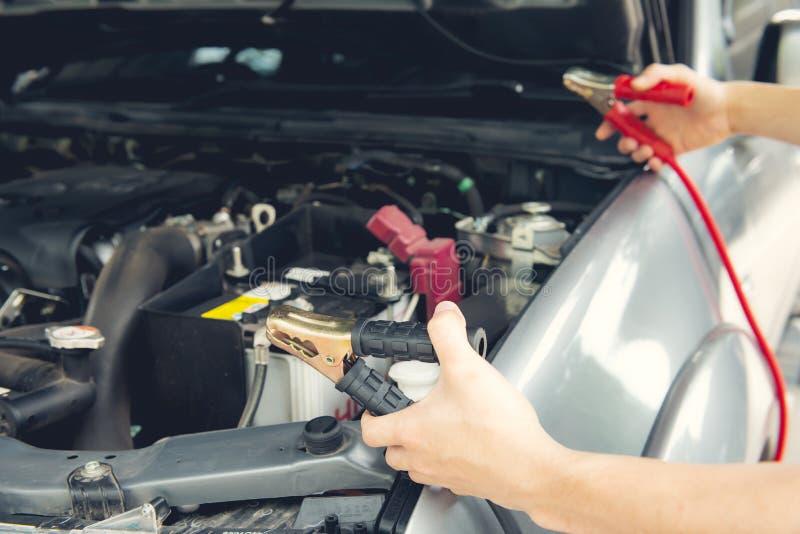 Laddande bilbatteri med kablar för elektricitetshoförkläde royaltyfri foto