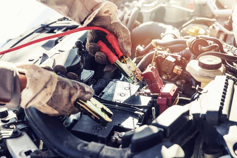 Laddande dött bilbatteri med förklädekablar royaltyfria foton