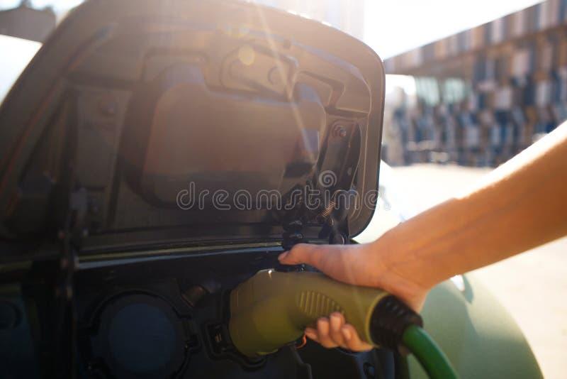 laddande elektriskt stationsmedel Den manliga handen som laddar en elbil med tillförselen för maktkabel, pluggade in eco arkivfoton