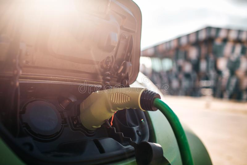 laddande elektriskt stationsmedel Ladda en elbil med tillförselen för maktkabel som in pluggas Eco-vänskapsmatch bil för royaltyfri bild