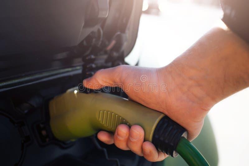 laddande elektriskt stationsmedel Närbilden av handen som laddar en elbil med tillförselen för maktkabel, pluggade in eco fotografering för bildbyråer